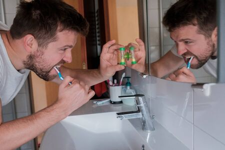 Young man with toothbrush cleaning teeth and looking to mirror at home bathroom