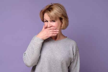 woman with puzzled look covering her mouth trying to keep secret.