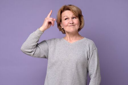 Middle age senior woman standing pointing finger up with successful idea. Stockfoto