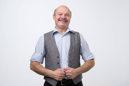 Elderly hispanic man with mustache in shirt and vest smiling confident at camera. Positive facial human emotion. Stockfoto