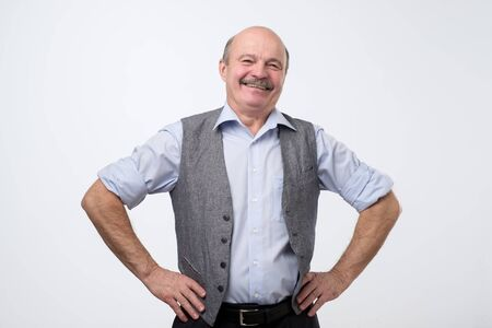 Elderly hispanic man with mustache in shirt and vest smiling confident at camera. Positive facial human emotion. Foto de archivo