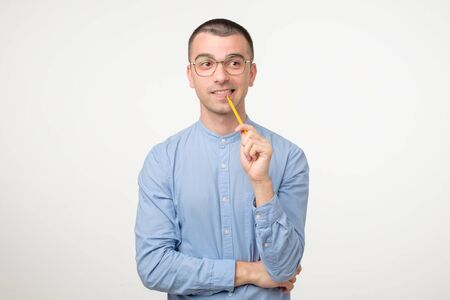 Young hispanic man in glasses is thinking about something with pencil generating idea. Studio shot