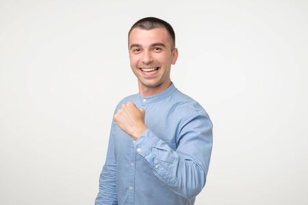Happy successful young hispanic student showing fist. He has done all his tasks and is satisfied with results. Studio shot Stockfoto