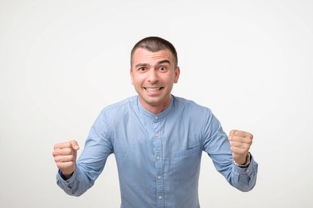 Portrait Of Smiling Man With The Fists Up Against A White Background Stockfoto