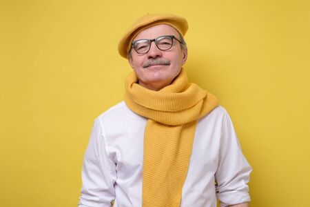Hispanic senior man in yellow beret and scarf looking with a smile at camera.
