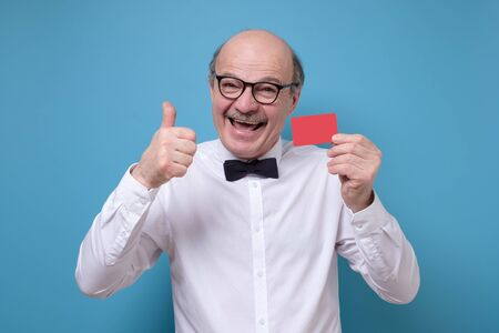 man showing blank visiting or credit card gesturing thumb up
