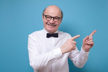 senior man with satisfied expression, indicates with fore fingers aside Stockfoto