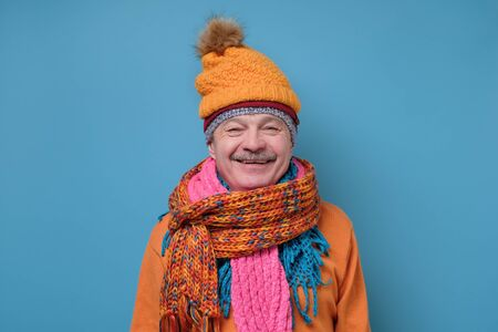 funny senior man in several hats and scarfs on blue background