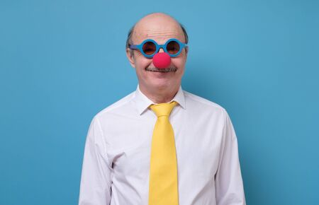 Handsome senior man in clown nose yellow tie and blue sun glasses ready for Firts of April, day of Fool. Studio shot on blue wall.