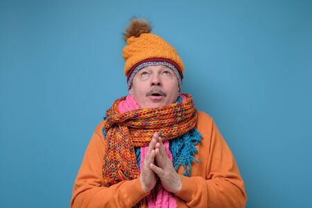 Handsome funny senior man in several hats and scarfs looking up in surprise