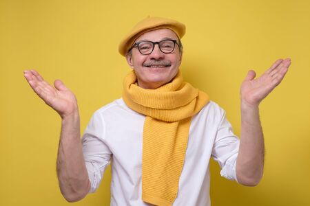 man in glasses and yellow beret and scarf spreading hands up welcoming friend Stockfoto