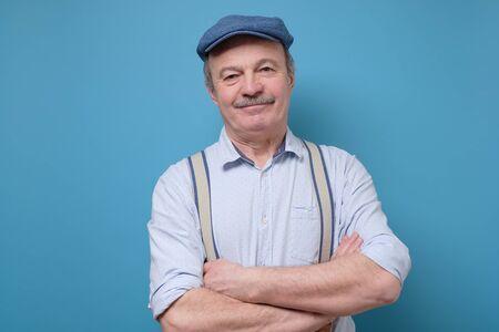 Portrait of friendly confident senior man in summer hat