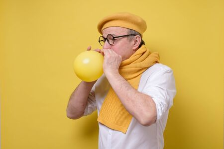 man in yellow beret and scarf getting ready to the party blowing a balloon.