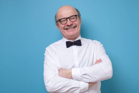 Happy hispanic bald man in glasses smiling at camera standing with folded hands.