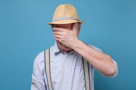 Senior man in summer hat covering eyes