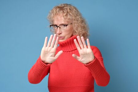Middle age mature woman wearing red sweater and glasses doing stop gesture Imagens