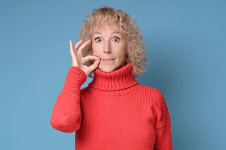 Caucasian mature woman shutting mouth and lips shut as zip with fingers.
