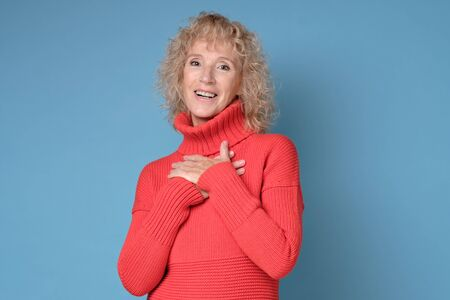 female teacher keeps hand on chest as being satisfied to recieve compliment
