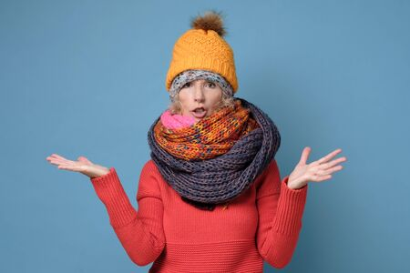 Mature woman in several hats and scarfs frowning being displeased and offended.