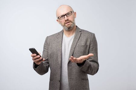 Mature frowning disgusted man surfing smartphone in dislike.