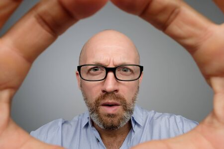 Bald mature guy in gray casual shirt discovering hidden camera.