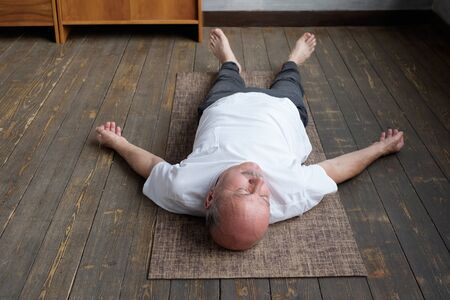Yoga. Senior man meditating on a wooden floor and lying in Shavasana pose. Attractive yogi working out at home, doing yoga