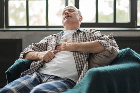 Senior hispanic man having a heart attack Stock Photo
