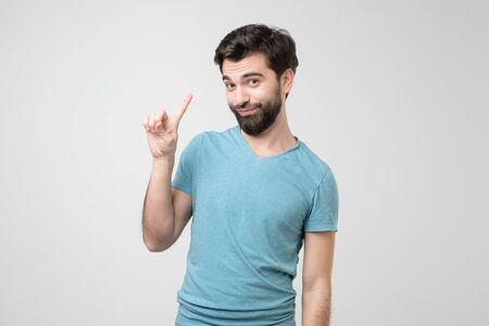 Young handsome hispanic man with beard pointing with finger up and angry expression, giving good advice