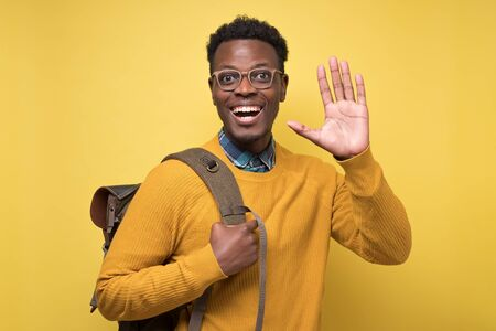 Well hior good bye concept. Young african american welcoming student man toothy smiling and showing five fingers at camera. Studio shot on yellow wall.
