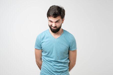 Serious young hispanic man with raised eyebrow having doubts or distrust. Studio shot on gray wall. negative facial human emotion.