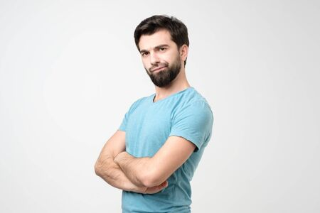 Young hispanic man frowning face in displeasure, keeps arms folded. Studio shot 写真素材