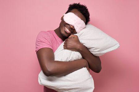 african american black man sleeping hugging a pillow wearing sleeping mask.