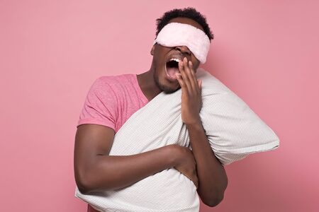 African american man yawning waking up holding pillow
