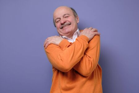 Pleased caucasian senior man in orange sweater hugs himself, has high self esteem feeling happy being alone. Studio shot