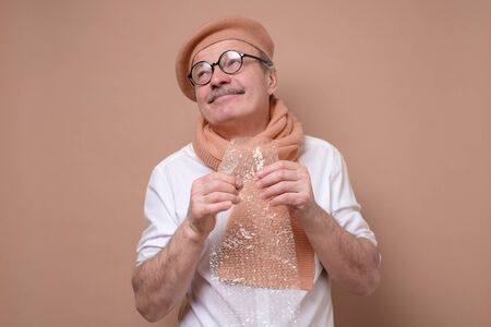 Senior man in glasses holding a piece of bubble plastic in his hand trying to relax and do not worry. Studio shot