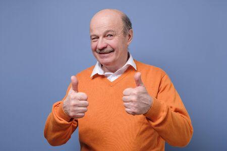 Handsome senior hispanic man holds his thumbs up approving choice. Studio shot