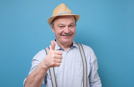 Positive senior hispanic man in summer hat showing thumb up approving your choice. Studio shot on blue wall. Positive facial human emotion.