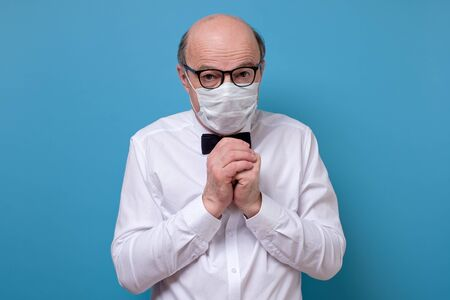 Portrait of senior sick old man in medical mask being afraid to be ill by coronavirus. Studio shot. Stok Fotoğraf