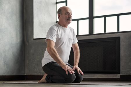 Senior hispanic man doing yoga exercise at home, sitting on floor in living room. Stay home during Stock Photo
