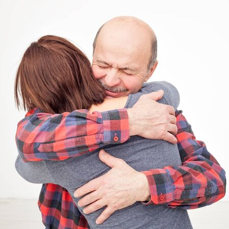 Adult daughter and older hispanic father hugging and cuddling with closed eyes close up, expressing love and gratitude, enjoying tender moment. Studio shot Stock Photo