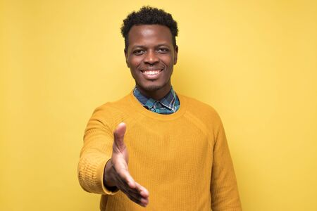 Black male reaching out toward camera to shake hands on yellow background