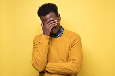 Young african man is hiding his face in the palms of his hands 版權商用圖片