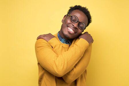 Pleased african american man hugs himself, has high self esteem