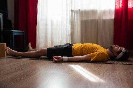 Young man meditating on a floor and lying in Shavasana pose at his living room. Stock Photo