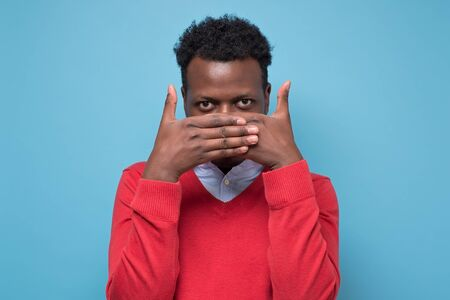 Attractive nice african young man closing his face with palm and peeping trying to see what is going on. Studio shot on blue wall.