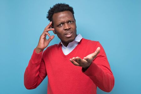 Pensive young african man against a blue background. What are you speaking about concept. Studio shot Standard-Bild