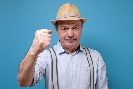 Senior man in summer hat angry and mad raising fist frustrated and furious. Rage and aggressive concept.