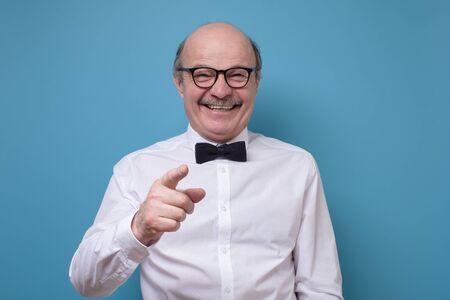 Senior hispanic man in glasses pointing finger on you. Studio shot on blue wall.