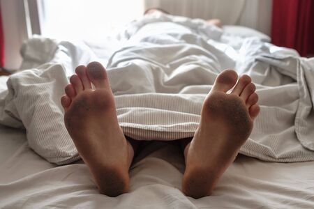 Dirty bare feet of a sleeping person showing out of the blanket on a bed. Hygiene or unsanitary conditions concept 版權商用圖片