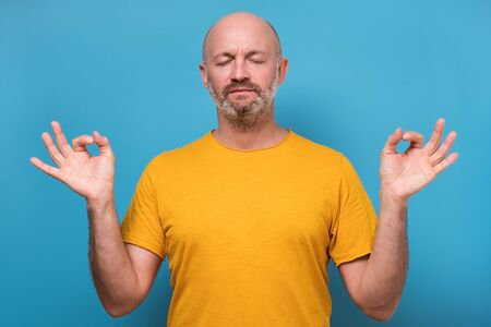man meditates tries to relax after hard working day, daydreams
